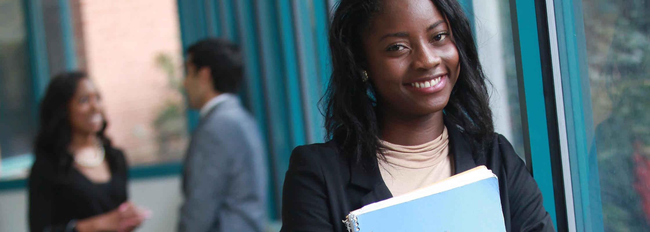 DSU student carrying textbook