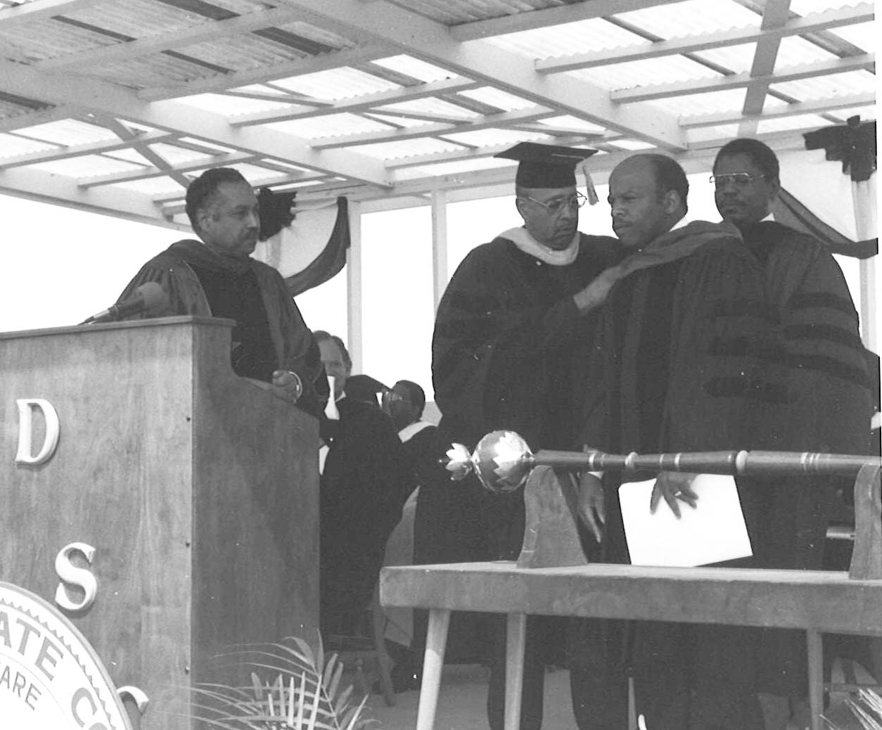 Dr. Ulysses S. Washington and Henry Tisdale place the honorary doctoral sash on John Lewis. Dr. William B. Delaware watches.