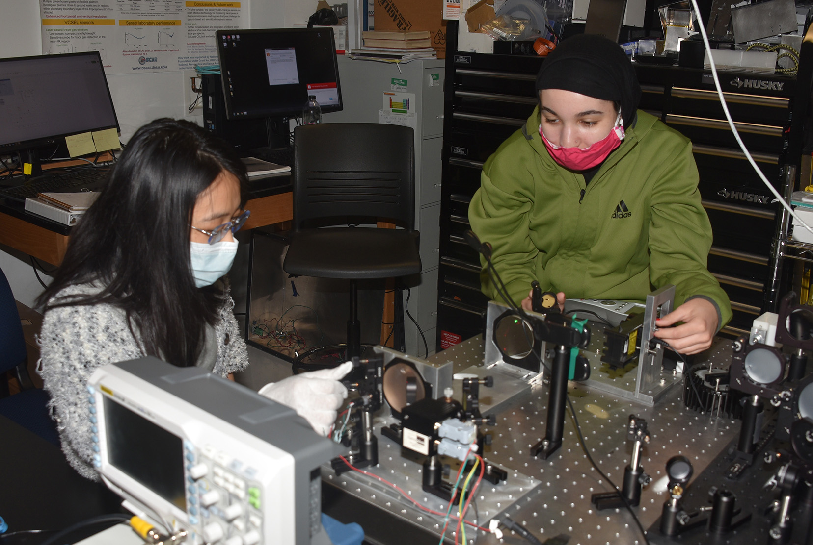 (L-r) Yue An, an optics graduate student from China, and Zayna Juracka, an engineering undergraduate and recent Early College High School graduate, are building a sensor that will measure air quality as part of an Air Quality Mapping summer program.
