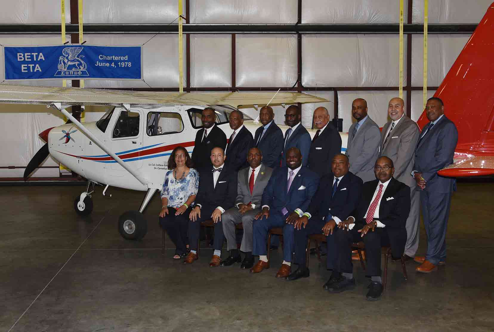 Beta Eta members pose at the Del State plane renamed after two of its members. (L-r, bottom row, Dr. Cornelius Gaither's daughter Carol Clark, Alfred Spencer, Collace Greene Jr., University President Tony Allen, William Allen, Wesley Wilson; (top) Tony Edwards, Dr. Karl Brockenbrough, Dr. Harvey White, Juan Roach, Theodore Greer, Dr. Michael Casson, Vincent Ross, and John Ridgeway.