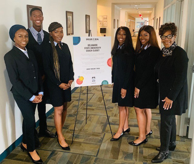 Del State students dress in the donated professional attire pose with Coach Foundaton's Peythia Stubbs.
