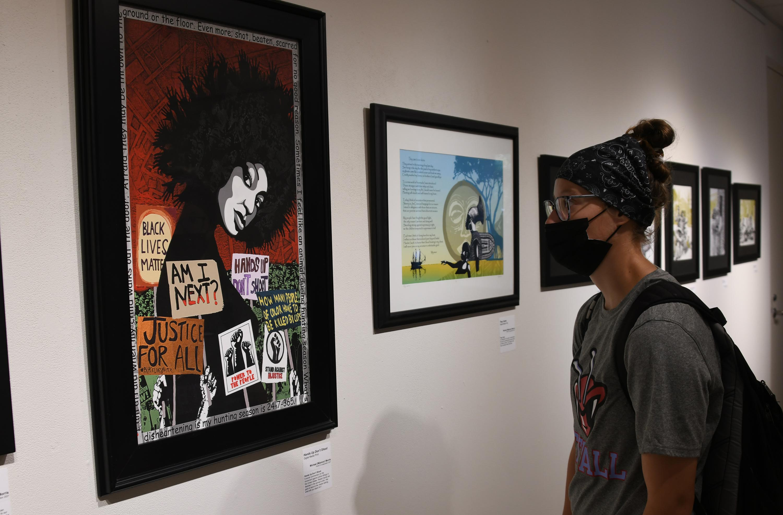 """Michael Morris' work """"Hands Up, Don't Shoot"""" draws the attention of a Del State student."""