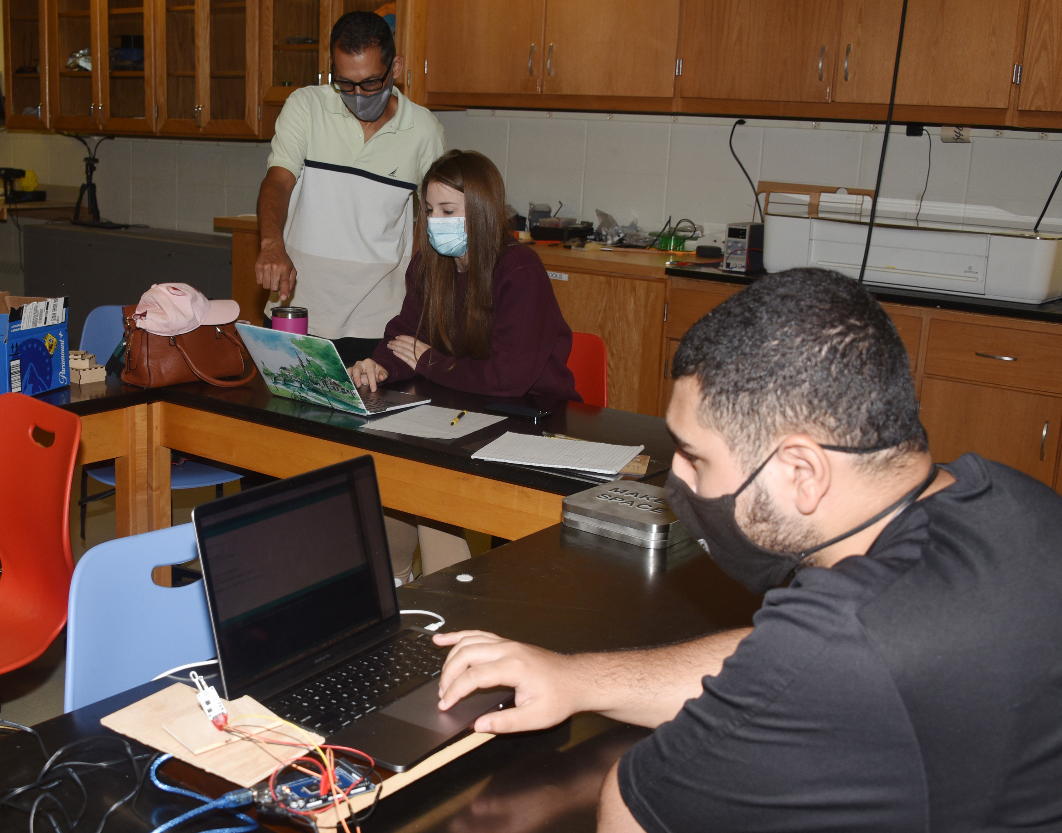 (L-r) Dr. Marwan Rasamny provides guidance to Sabrina Kruger and Abdullah Al-Rubaye in the Maker Space.