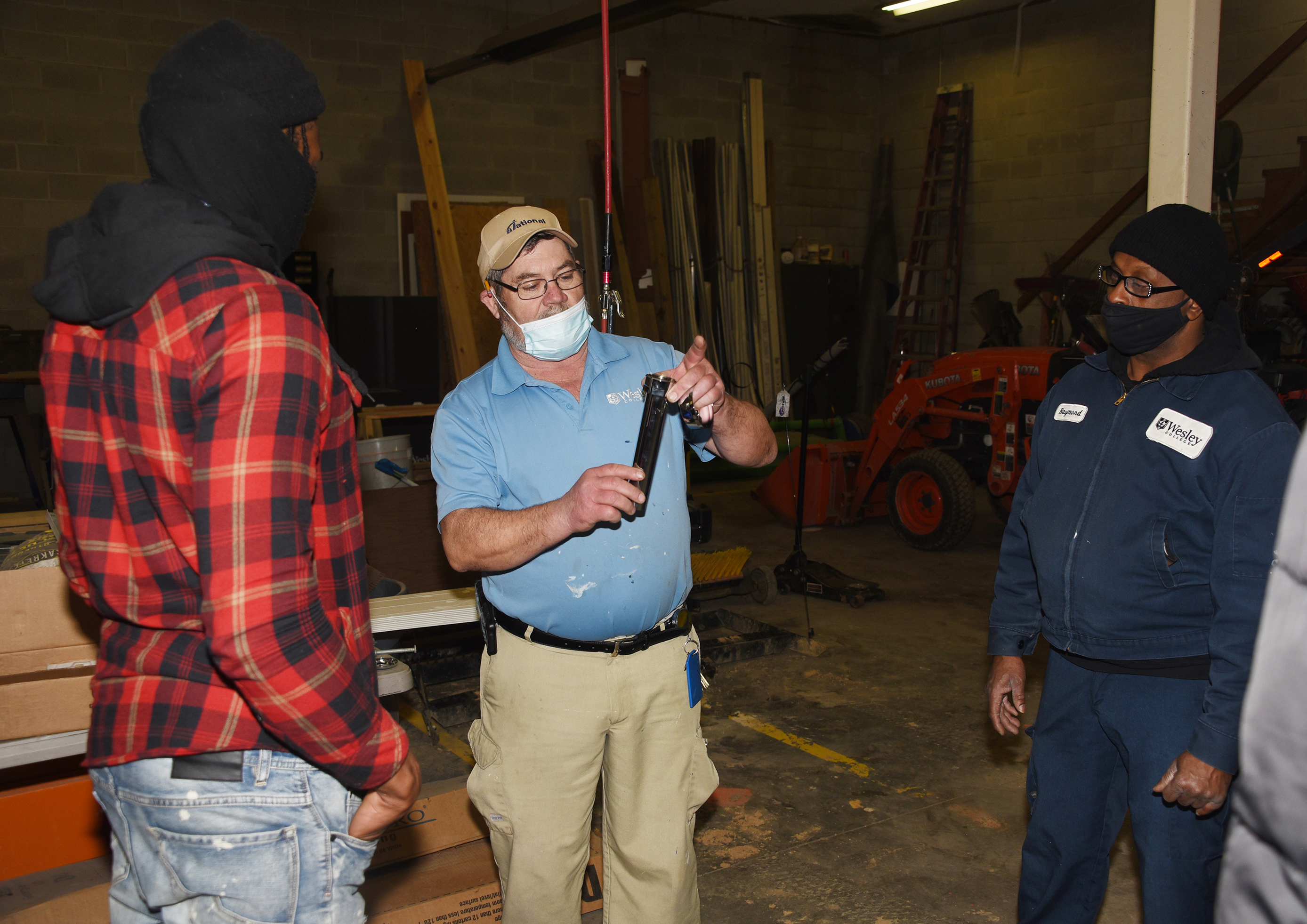 Frankie Martin, a Wesley College facilities worker, shares his plumbing knowledge with three P2A participants.