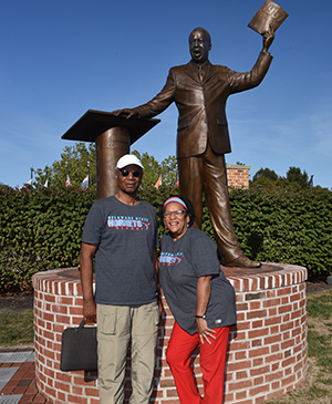 An alumni couple pose in front of the Dr. Jerome Holland statue during Homecoming Weekend.