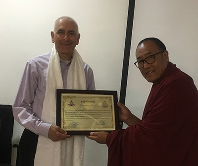 Dr. Matthew Bobrowski is recognized for his volunteer teaching by a representative of the Emory Tibet Science Initiative.