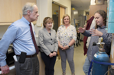 Dr. Michael Gitcho (left) updates US Sen. Tom Carper on Alzheimer research. Drs. Melissa Harrington and Sabrina McGary listen.