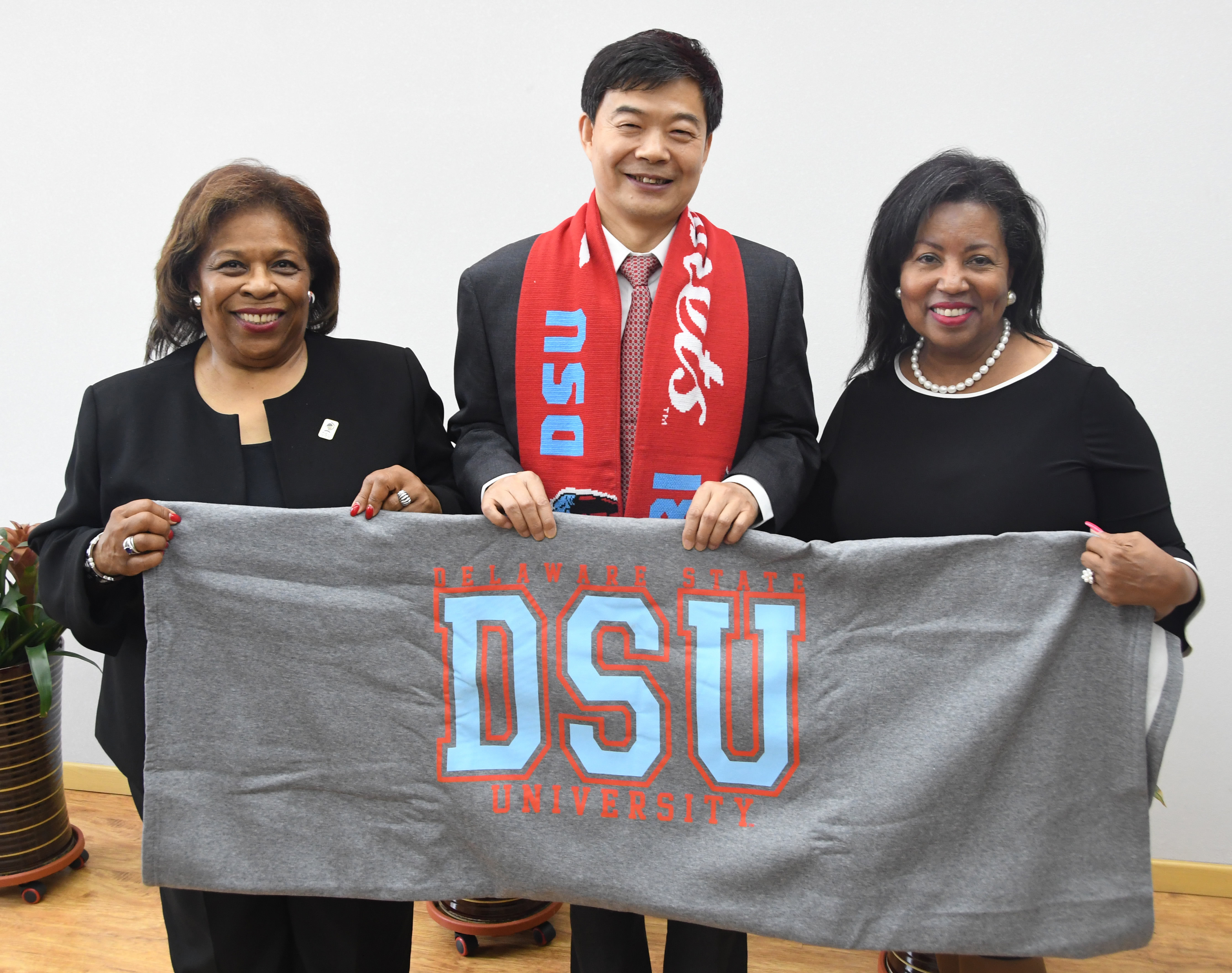 Dr. Wilma Mishoe, left, and Dr. Devona Williams present Su Zhongmin, president of the Changchun University of Science and Technology, with a DSU blanket and scarf.