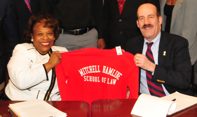 Dr. Wilma Mishoe receives a Mitchell Hamline shirt from its president, Mark C. Gordon.