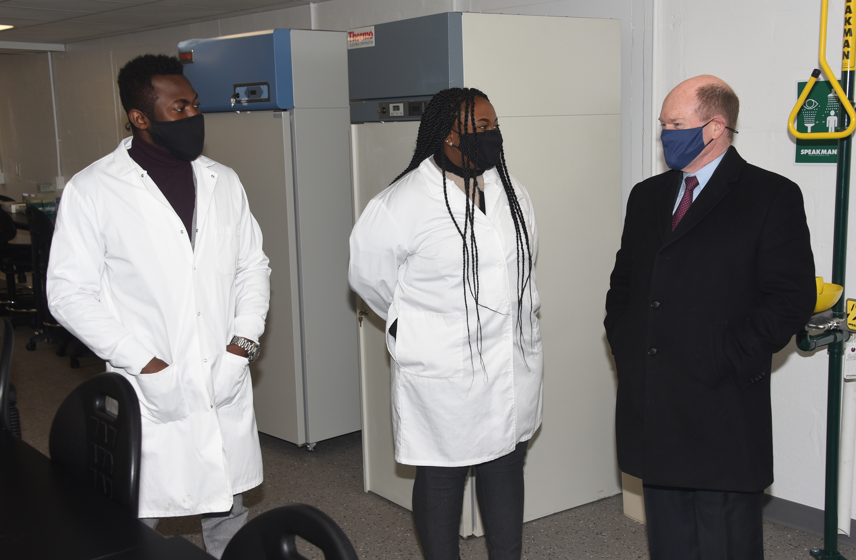 (L-r) Edward Addison and Audrey Janga -- University Alumni who work in the lab -- talk about their work with Sen. Chris Coons.
