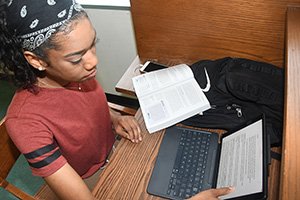 Mariah Adams, freshman biological sciences major, huddles with her iPad Pro i n the William C. Jason Library
