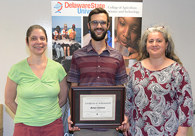 Brian Galvez (center) -- 1st place Graduate Oral Presentation, with Dr. Stacy Smith and Dr. Gulnihal Ozbay.