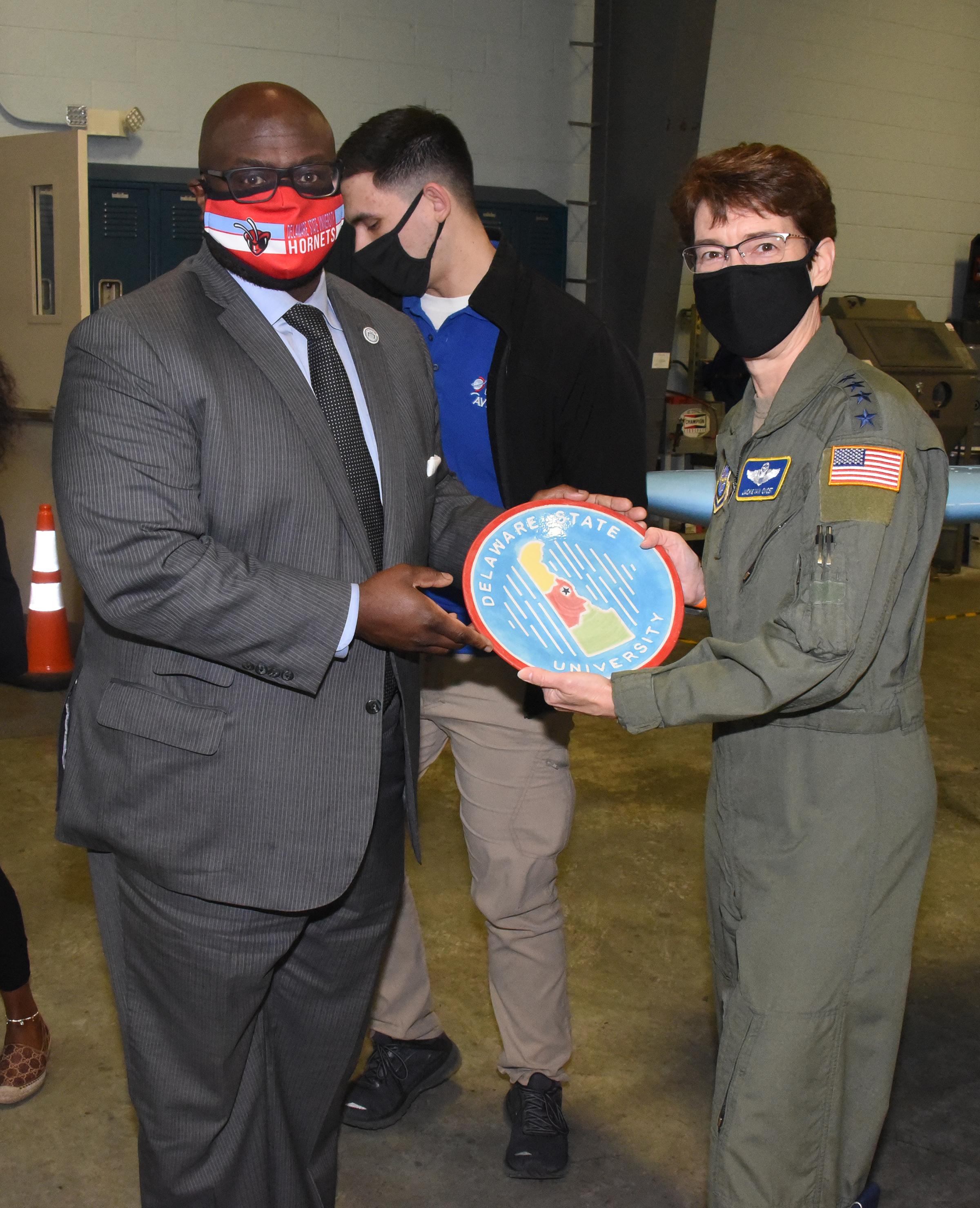University President Tony Allen presents Gen. Van Ovost with a Del State plate.