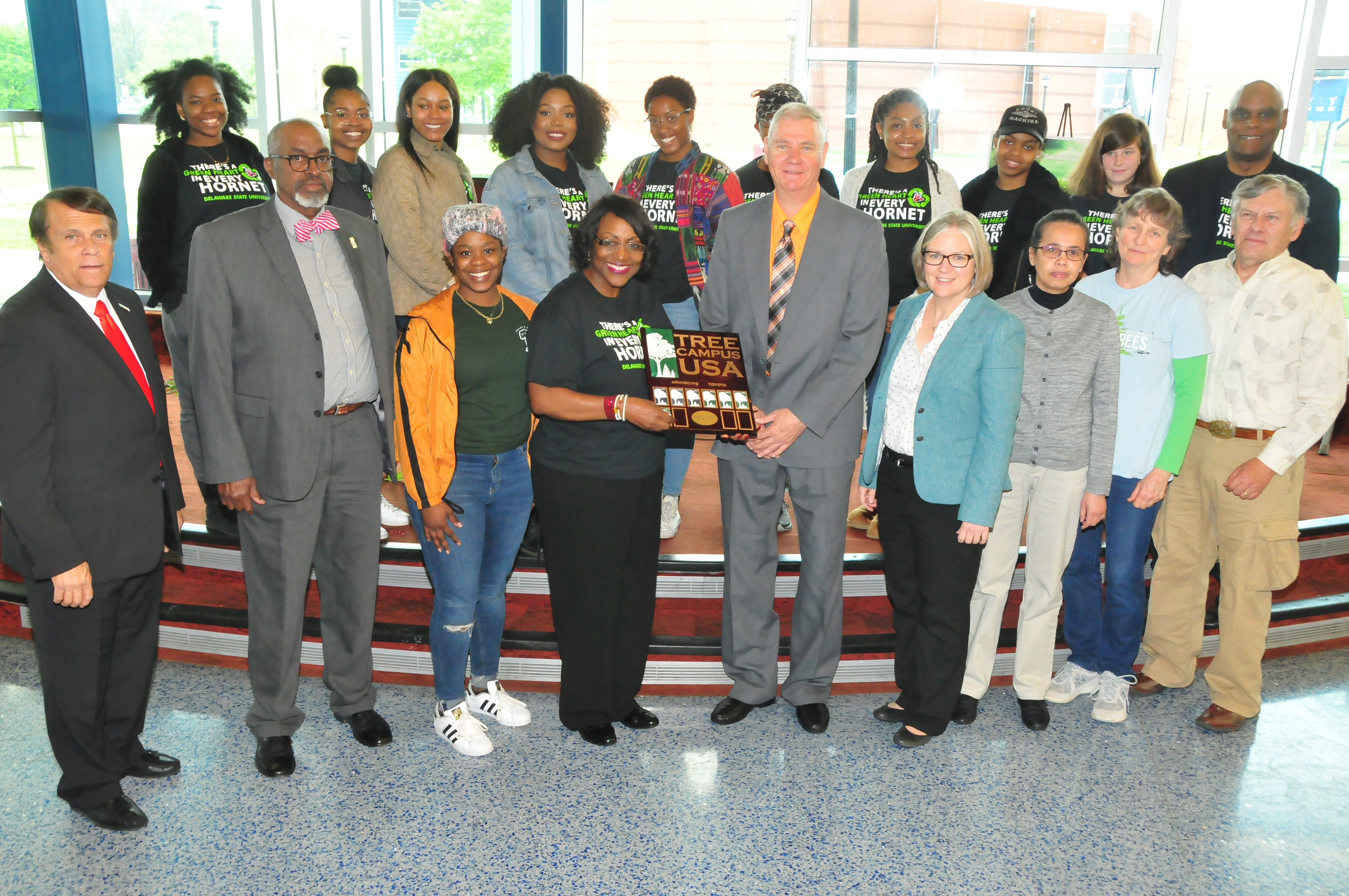 Dr. Vita Pickrum (center) receives the Tree Campus USA renewal designation on behalf of DSU from Dr. Michael Valenti, Delaware state forester. They are flanked by other DSU officials and Roteract and Interact student organizations.