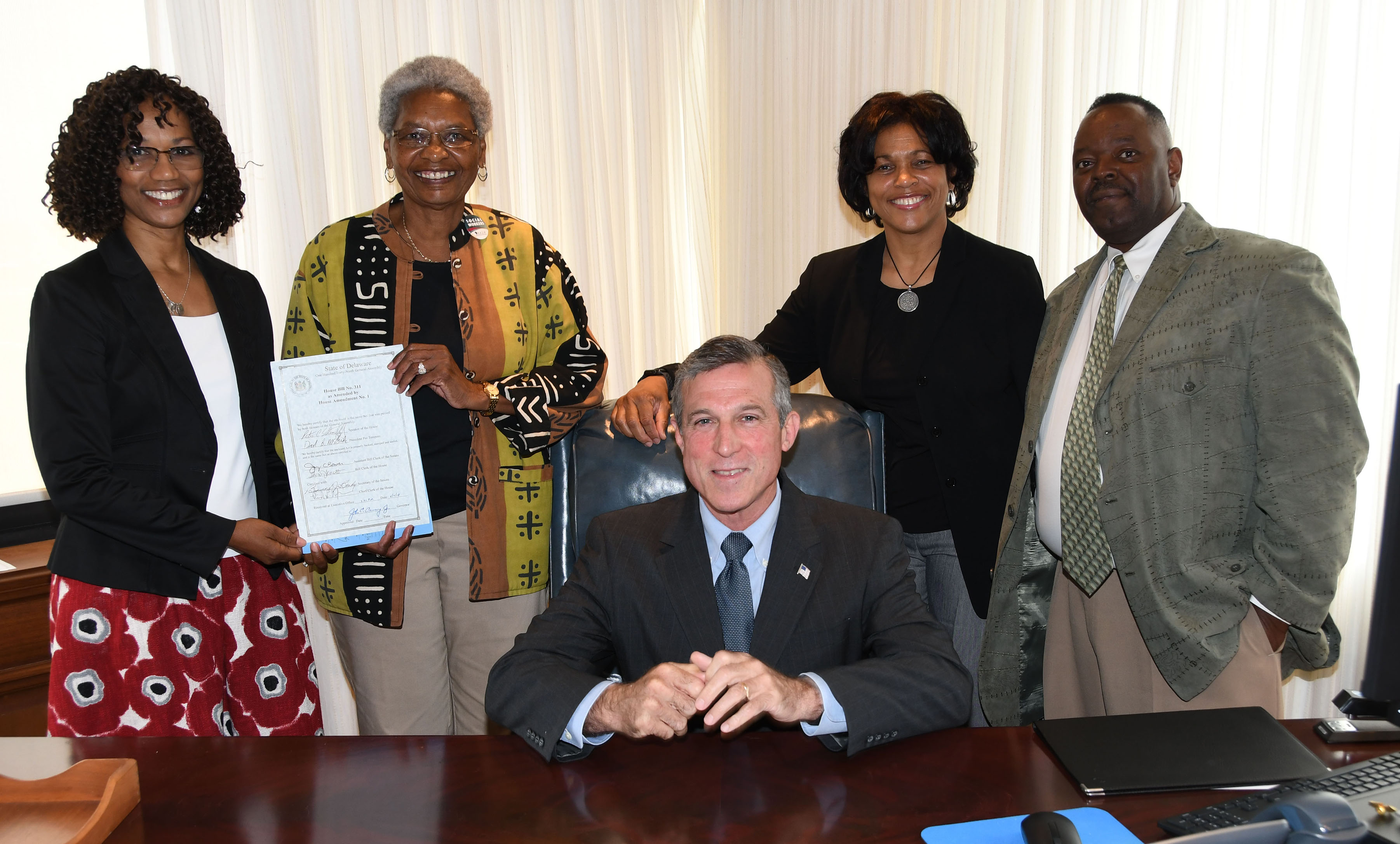 Gov. John Carney poses with the NASW-DE subcommittee -- all DSU folks -- who were instrumental in the passage of HB 311. Standing from l-r: Dr. Sheridan Kingsberry and Dr. Marlene Saunders holding the signed legislation, along with Dr. Fran Franklin and Philip Thompson.