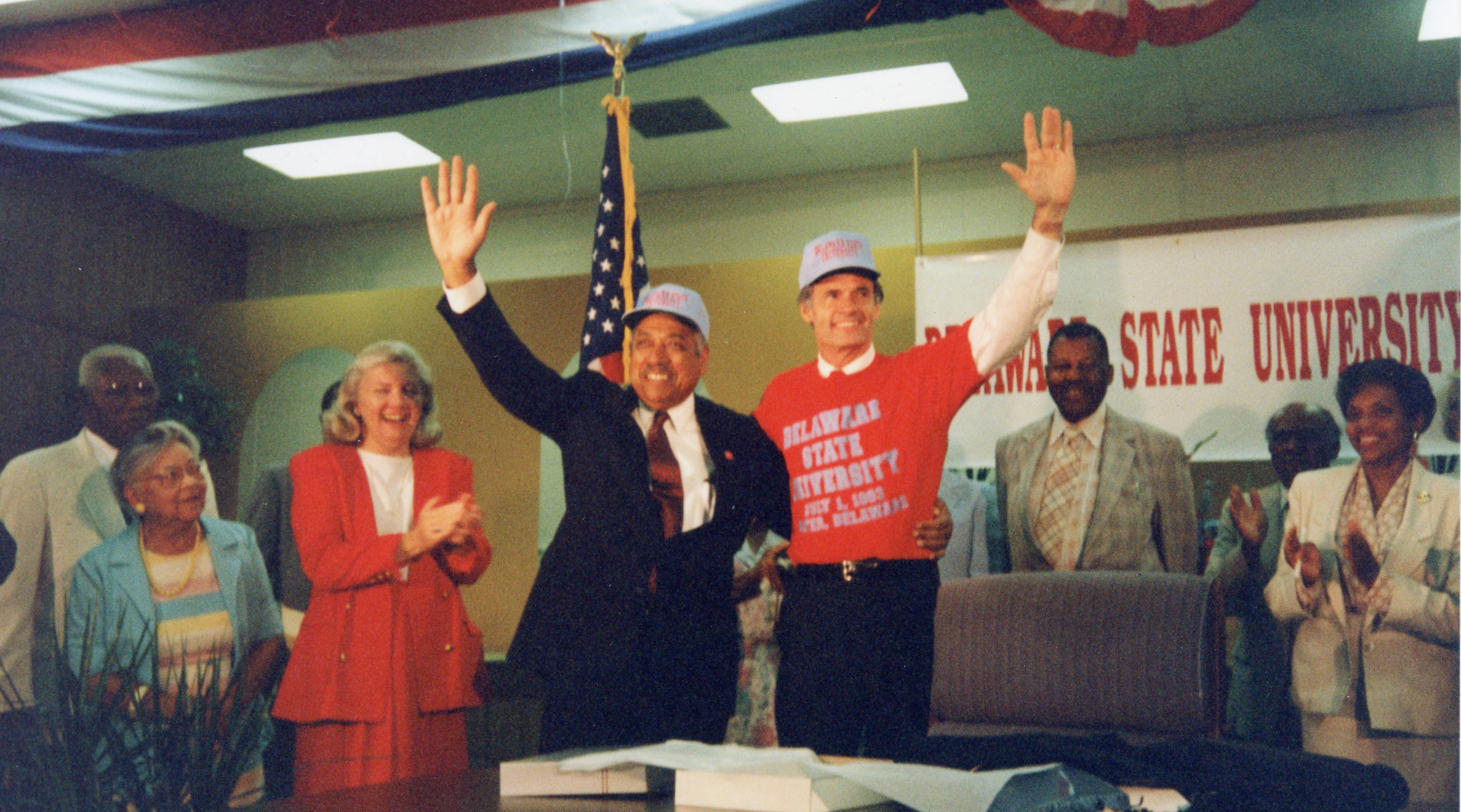 On July 1, 1993, William B. DeLauder, president of Delaware State University, waves with Gov. Tom Carper at the signing of Senate Bill 138 which changed Delaware State College to Delaware State University. Looking on in the background, from left, are Senator Herman Holloway Sr., Hattie Mishoe, Representative Nancy Wagner, James C. Hardcastle and Vermell DeLauder.