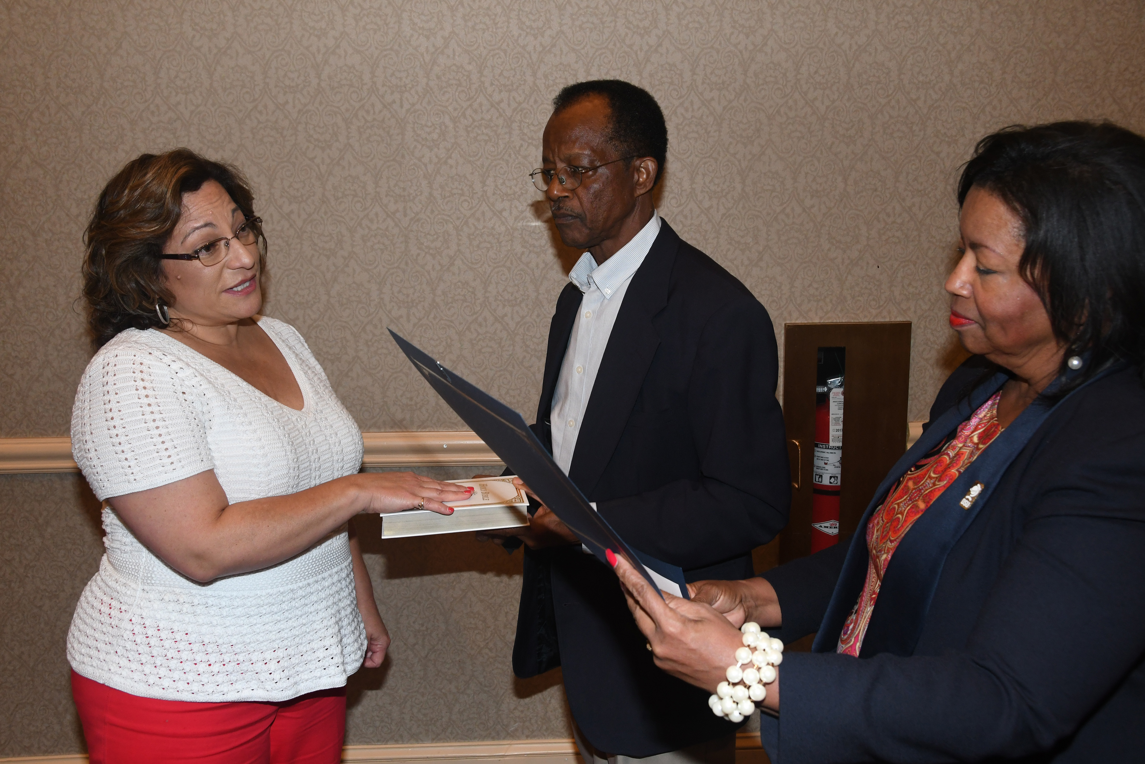 New Board of Trustees member Margie Lopez Waite (l) is sworn in by Board Chair Dr. Devona Williams during the Sept. 20 meeting. Trustee Harold Stafford holds the bible.