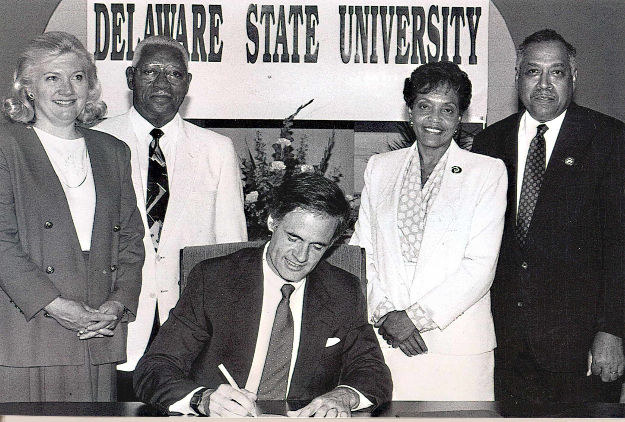 Dr. Willliam B. DeLauder (far right), the University's eighth president, stands with state Rep. Nancy Wagner, state Sen. Herman Holloway Sr., and his wife Vermell, as then-Gov Tom Carper signed legislation renaming the College to Delaware State University. Dr. DeLauder passed away on May 21.
