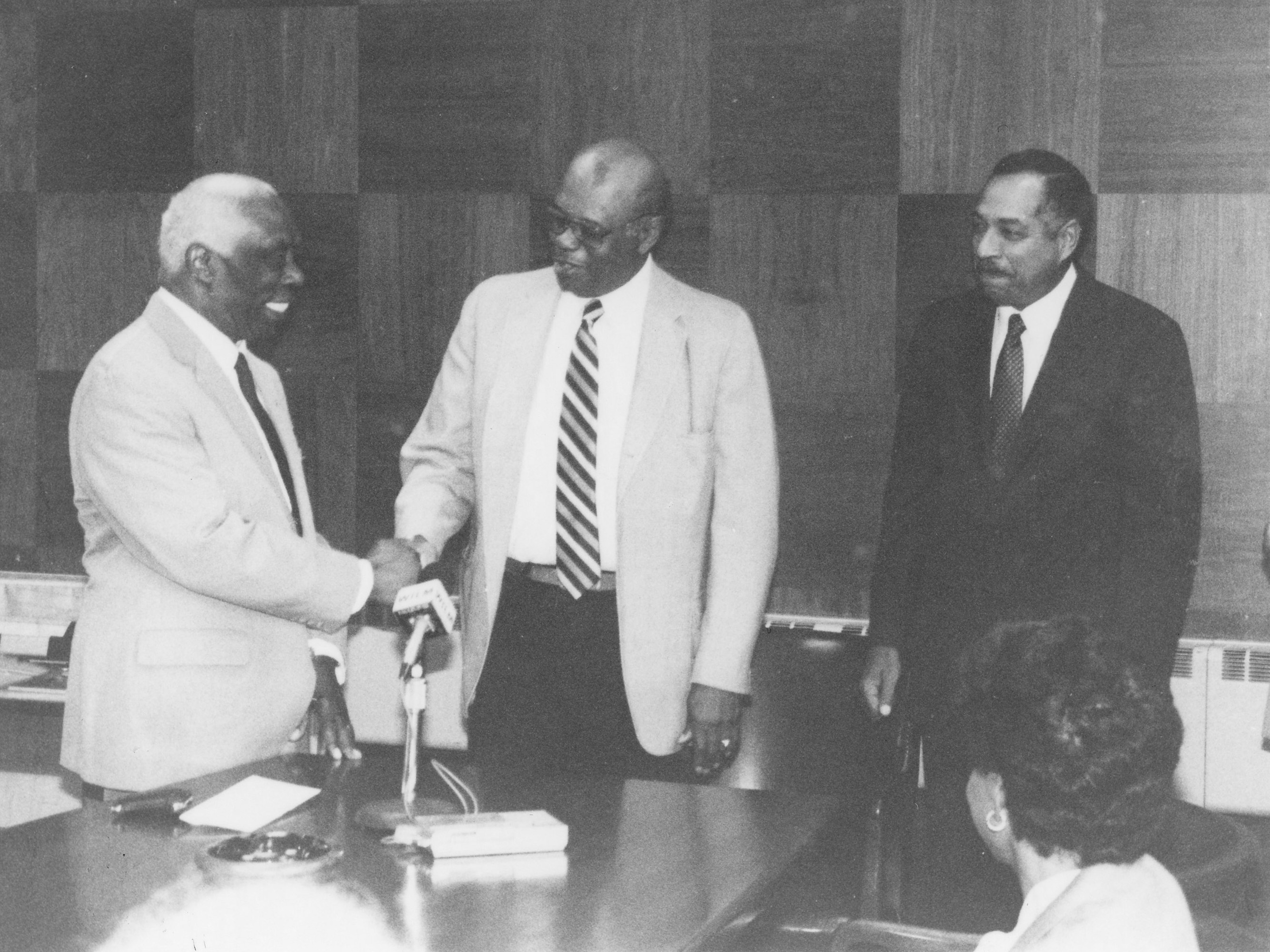 The historic 1987 passing of the presidential torch between then-outgoing DSC President Luna I. Mishoe (l) and his successor Dr. William B. DeLauder (r). Then-Board of Trustees President William Dix (center) shakes Dr. Mishoe's hand.