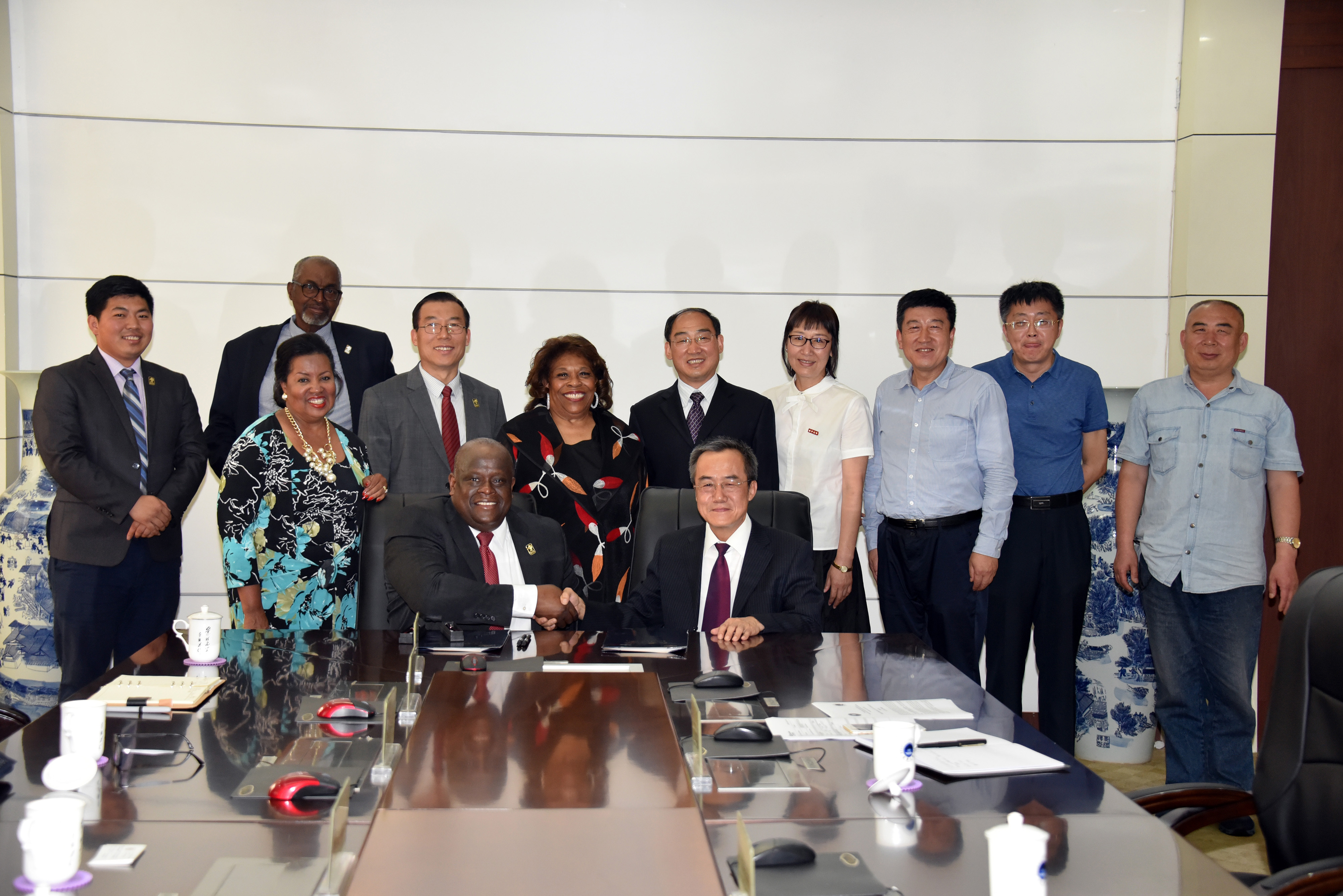 Tony Boyle, Vice President of Strategic Enrollment Management, and JiZong Qi, Vice President of Beihua University of China, shake hands after signing an agreement that establishes a joint English Language Institute in that Far East country.