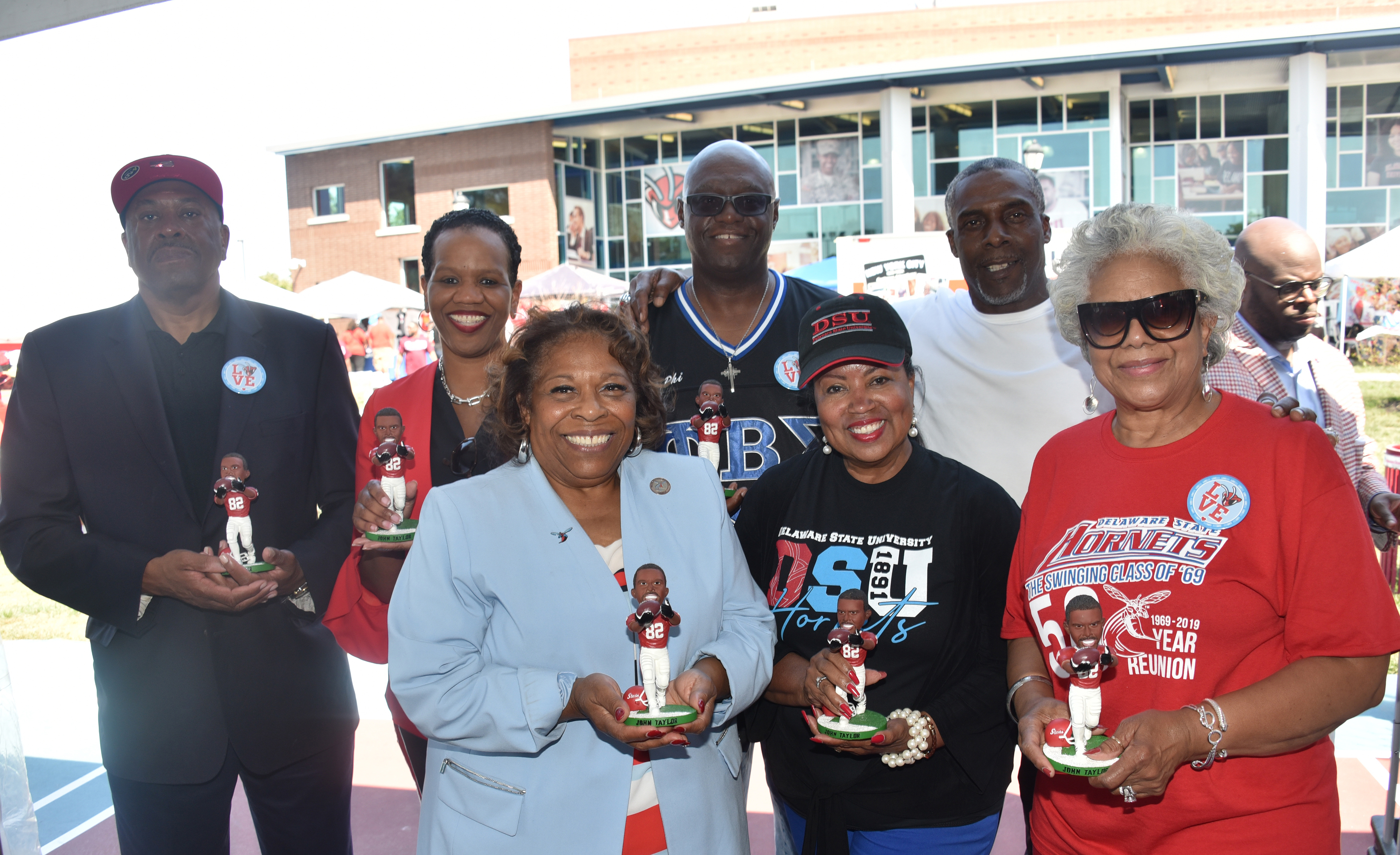 Hornet football alumnus and former NFL star John Taylor (2nd from the right) presents members of the University Board of Trustees and Dr. Wilma Mishoe with a signed bobble head likeness of himself.