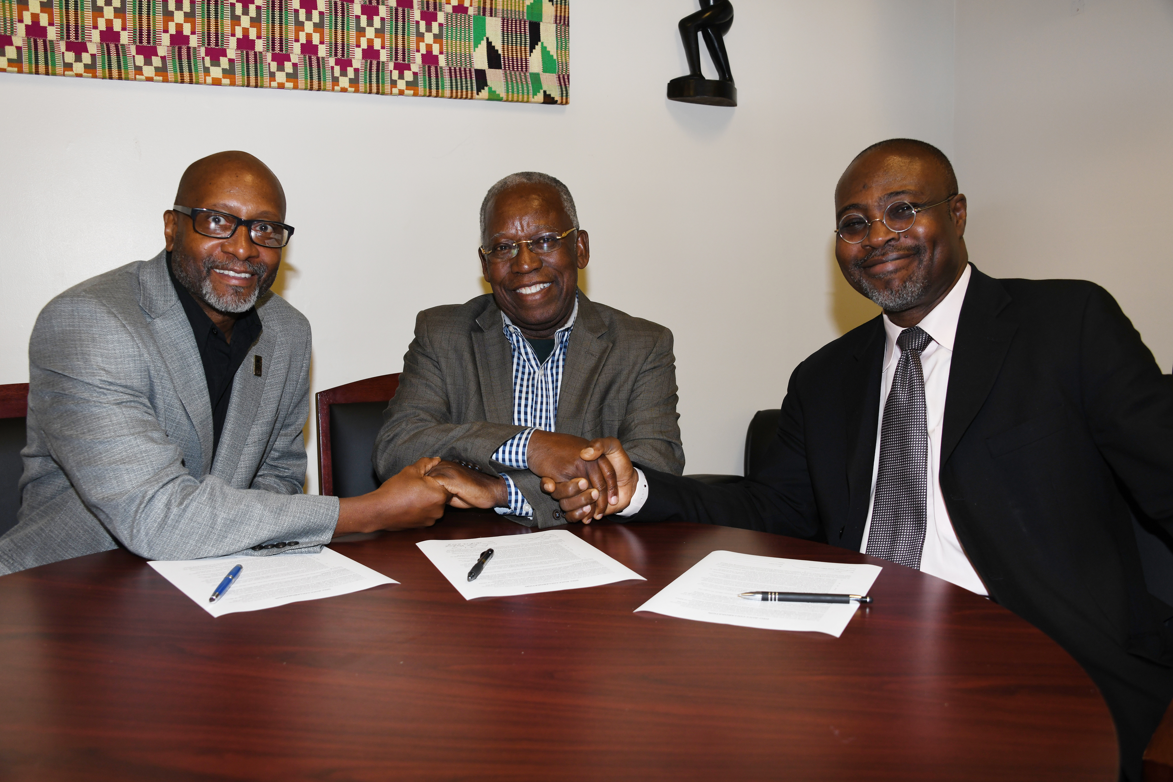 (L-r) Ezrah Aharone, director of the University's Center for Global Africa; Kojo Yankah, founder of the African University College of Communications in Ghana; and Dr. Akwasi Osei, associate dean of the College of Humanities, Education and Social Sciences, shake hands after signing a collaboration agreement between the two institutions.