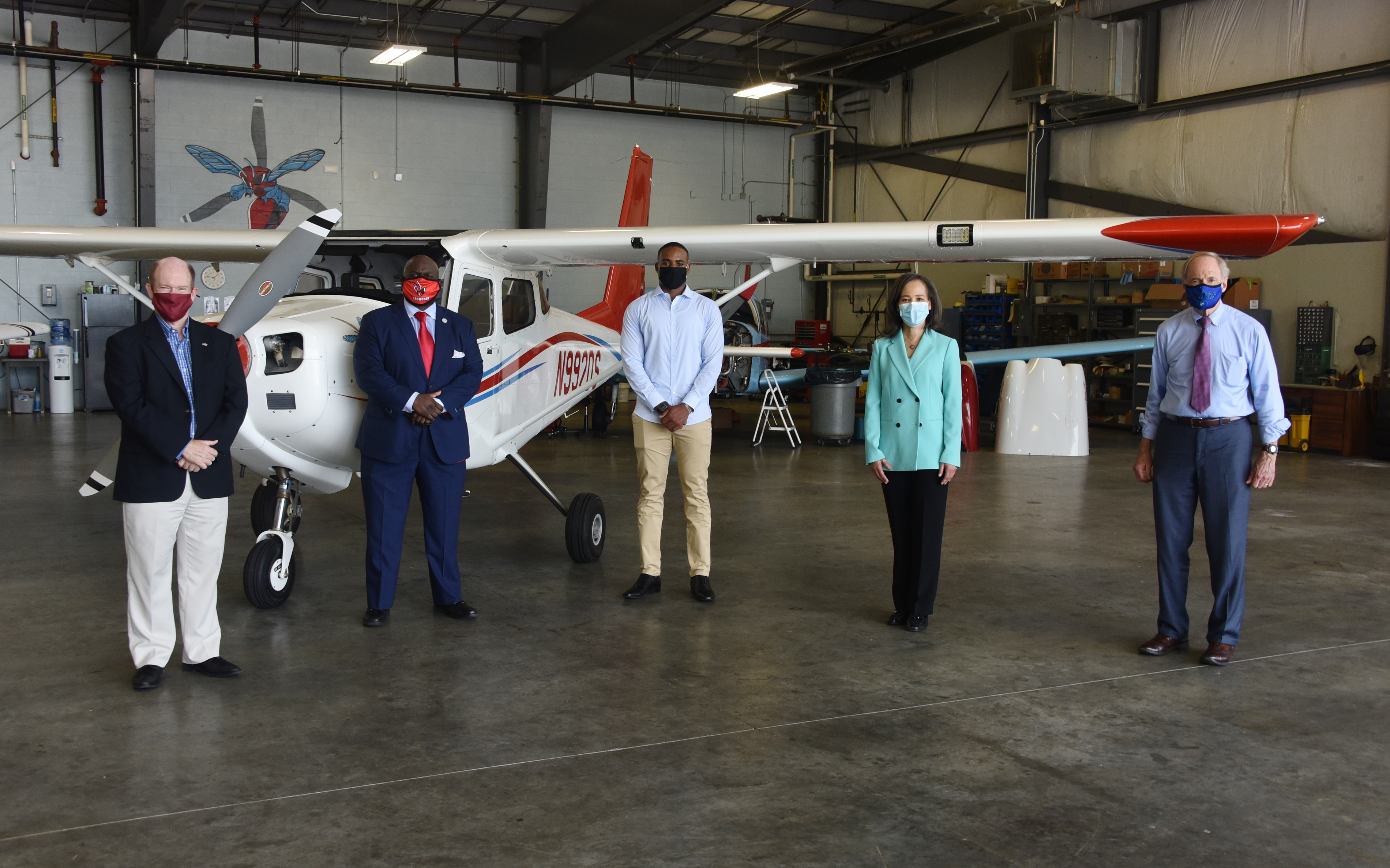 (L-r) U.S. Chris Coons, University President Tony Allen, Aviation freshman Tajay Kelly, U.S. Rep. Lisa Blunt Rochester, and U.S. Sen. Tom Carper pose with adherence to social distancing, after an event in the Daniel Coons Hanger at the Delaware Airpark where the talked about The Flight Act and how it would benefit Del State's Aviation Program.