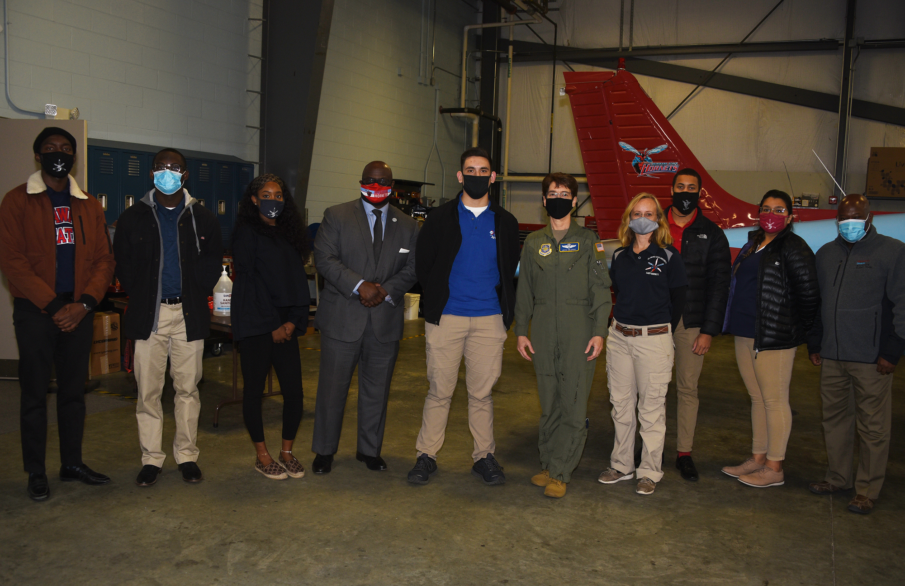 (L-r) Ian Teray Tcheliebou, Darrell Machison, Jalyn Clark, Dr. Tony Allen, Matthew Cunningham, Gen. Jacqueline D. Van Ovost, Cindy Blair, Mekhi Howard, Eliana Rothwell, and Aviation Program Director Lt. Col. (ret.) Michael Hales, pose for a photo after the four-star general gave an address at the Delaware Airpark
