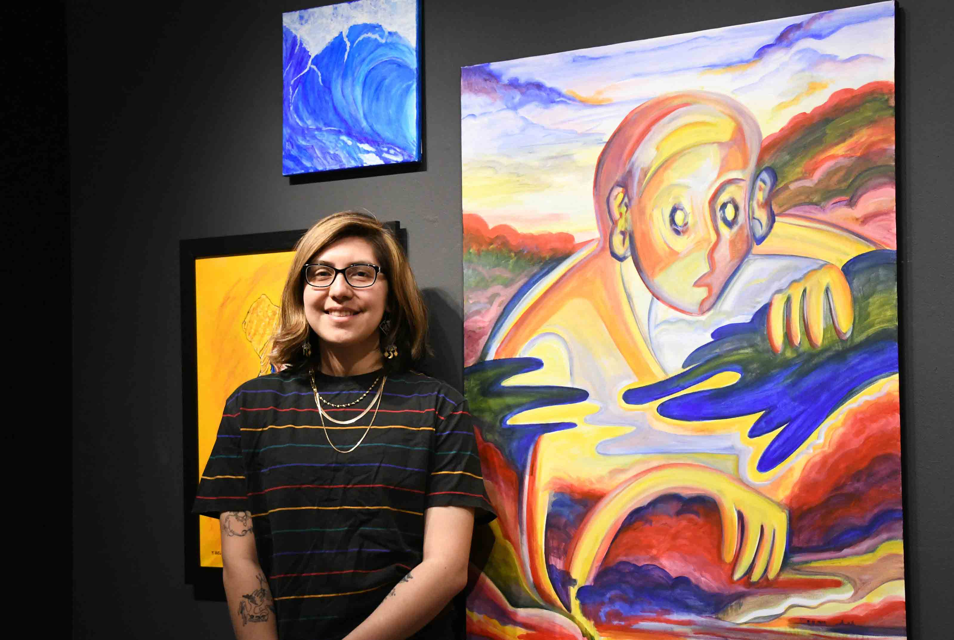 """Kiara Florez stands next to her painting """"The Wanderer,"""" one of the works on display in the Creative Connections exhibition at the Arts Center/Gallery."""