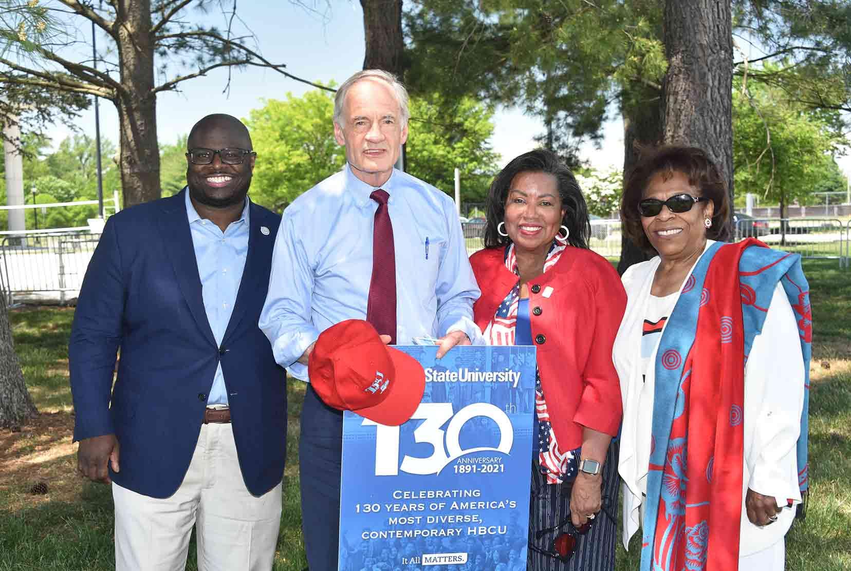 University President Tony Allen, U.S. Sen. Tom Carper, Del State Board Chairperson Devona Williams, and former University President Wilma Mishoe pose for a 130th Anniversary photo.