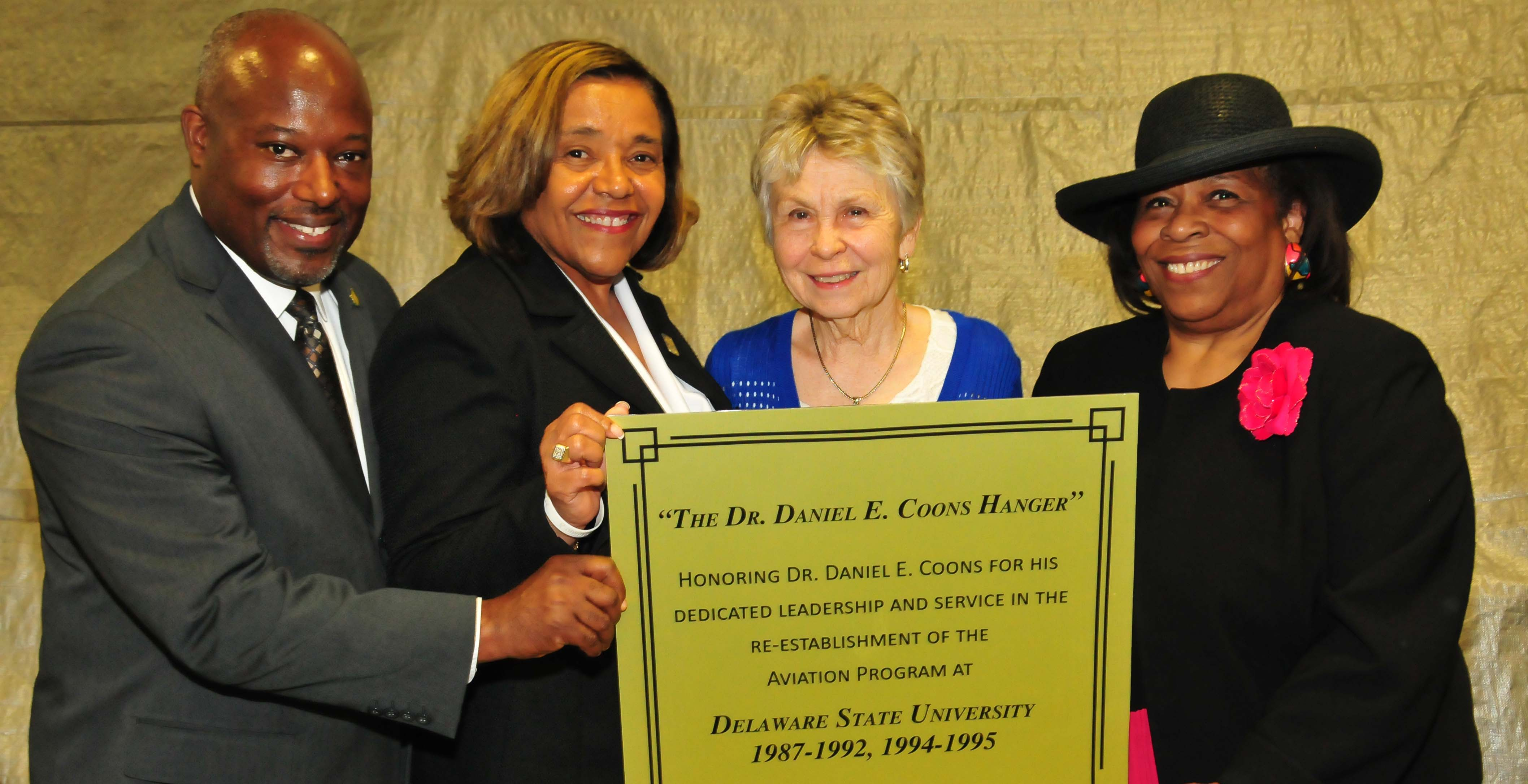 (L-r) Lt. Col. Michael Hales, director of the DSU Aviation Program; College of Business Dean Donna Covington; JoAnn Coons, widow of Dr. Coons; Dr. Wilma Mishoe, DSU Board of Trustees member, hold a copy of the plaque that is being created for the Daniel E. Coons Hangar.