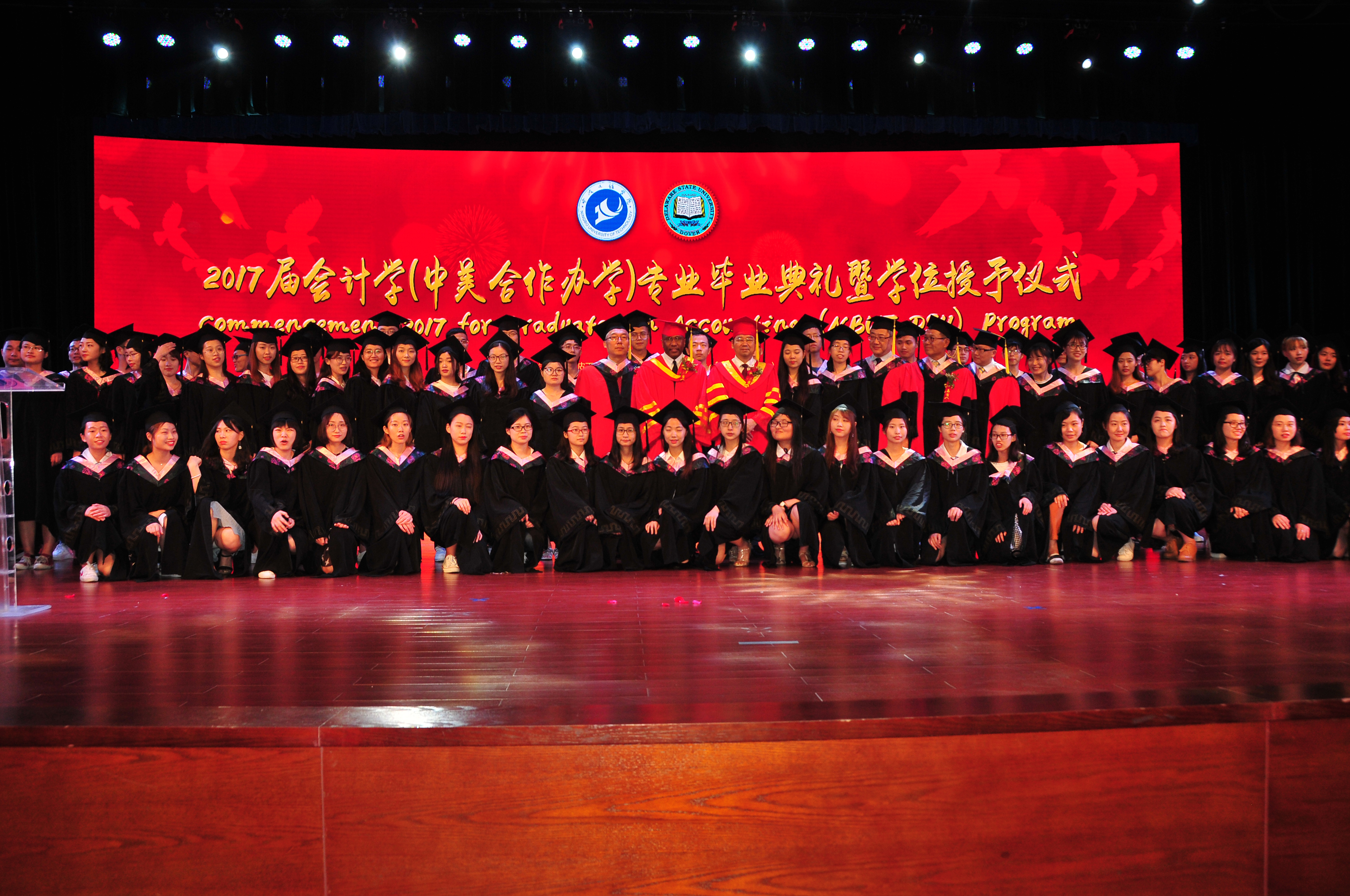 (Center) Dr. Fengshan Liu, DSU President Harry L. Williams and NBUT President Lyn Zhongda pose with the 81-member class of graduates from the DSU-NBUT Accounting Program