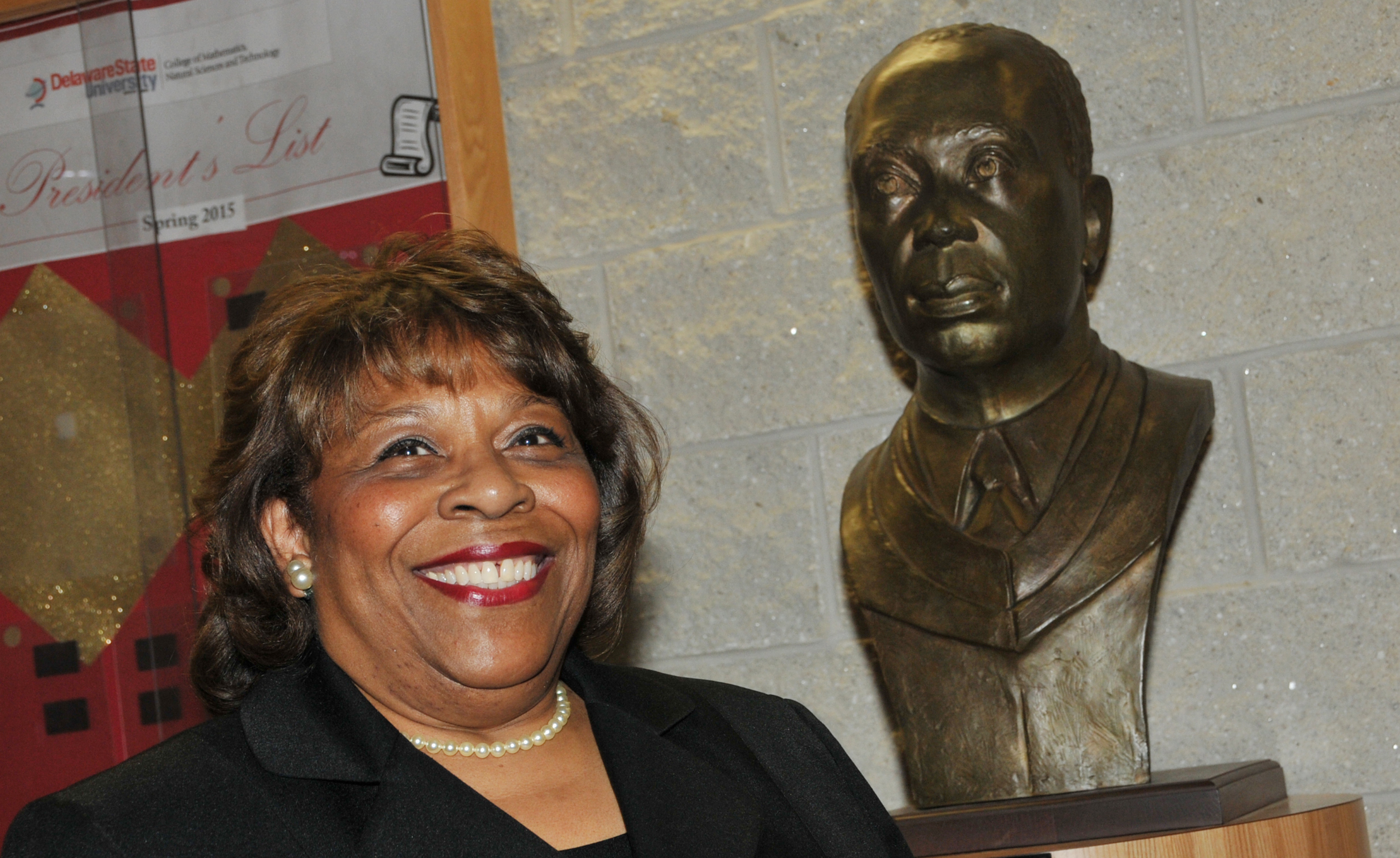 Dr. Wilma Mishoe, newly elected chairperson of the DSU Board of Trustees, stands next to the sculpture bust of her father Dr. Luna I. Mishoe, who was the president of then-Delaware State College from 1960-1987. Dr. Mishoe is the first woman to serve as the chair of the University's Board of Trustees.