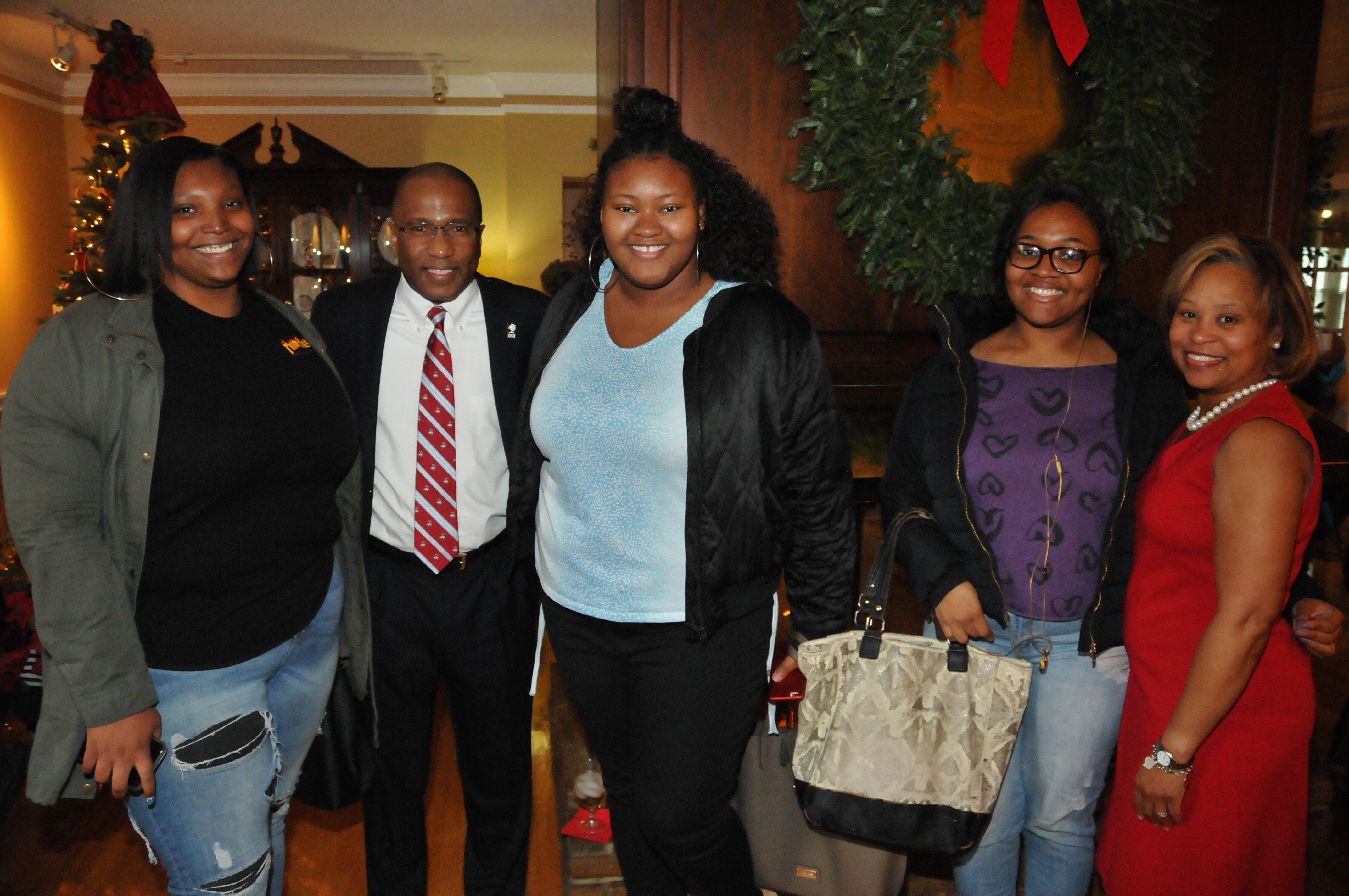 DSU President Harry L. Williams and First Lady Dr. Robin Williams pose with a group DSU students during their Christmas celebration at their residence.