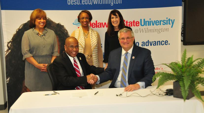 """<p>DSU President Harry L. Williams shakes hands with Red Clay School District Superintendent Merv Daugherty after signing an agreement to offer IT courses to high school students at <a href=""""mailto:DSU@Wilmington"""">DSU@Wilmington</a>.</p>"""